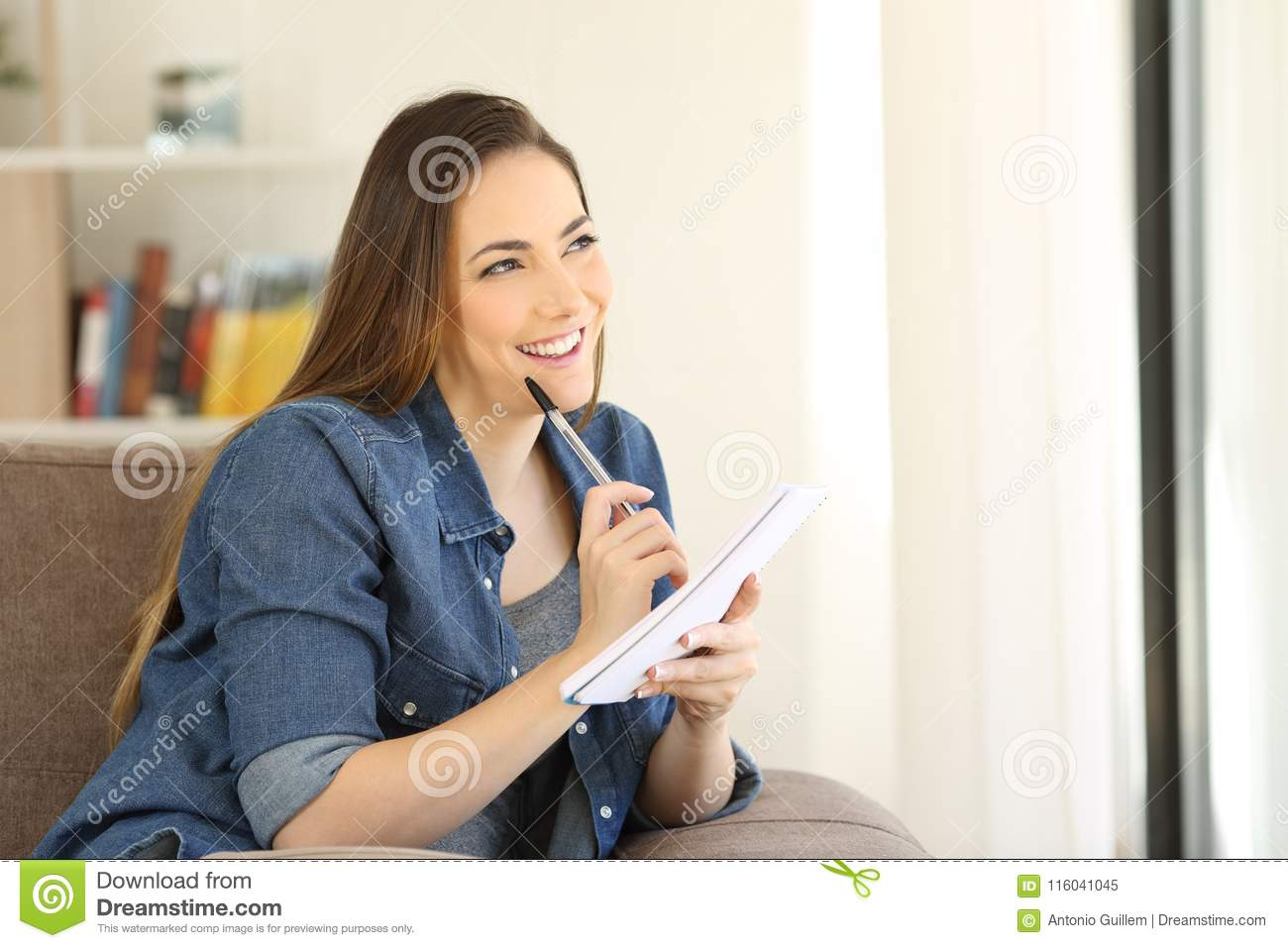 Happy woman thinking what to write in a notebook