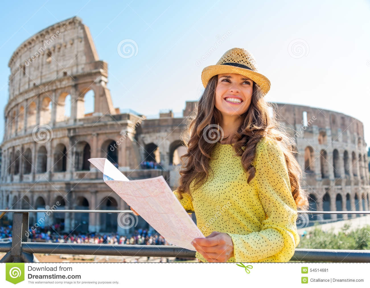 Happy woman tourist looking up from map at Rome Colosseum