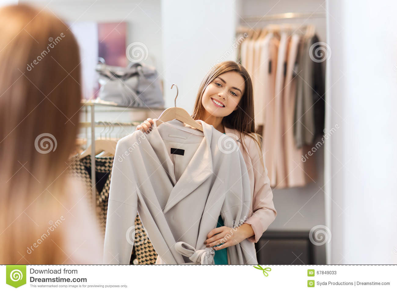 Happy woman trying coat at clothing store mirror