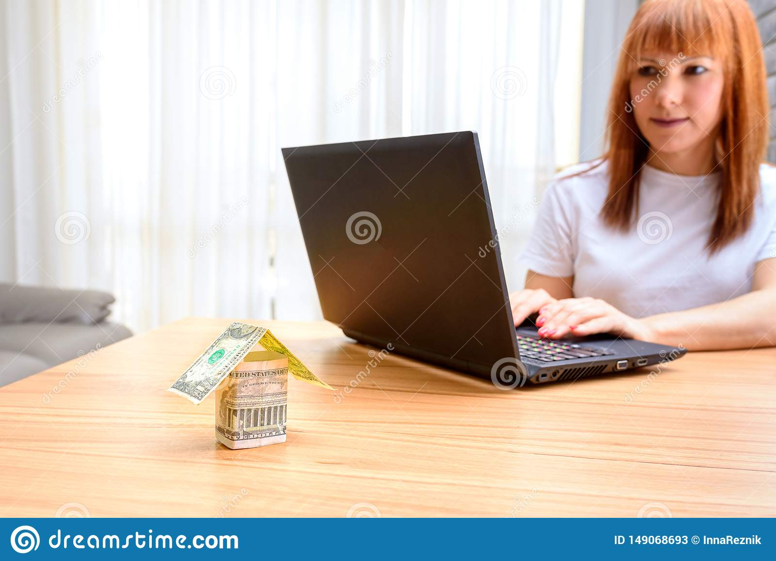 Happy woman using laptop. Concept of buying a home, real estate activity, meeting with advisor, new homes.