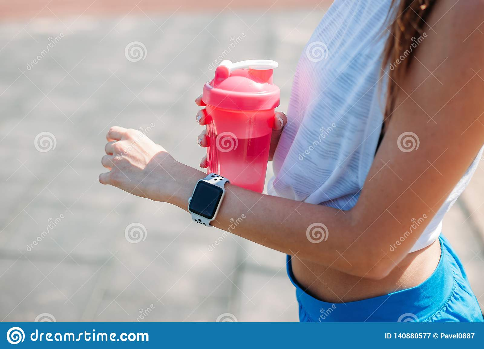 Happy woman using smartwatch for checks results in fitness app. Female athlete wearing sport tracker wristband arm. Healthy