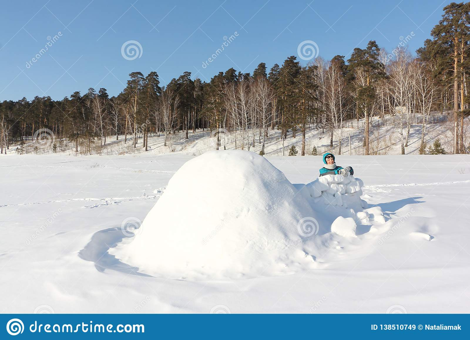 Happy Woman In Warm Clothes Building An Igloo On A Snow