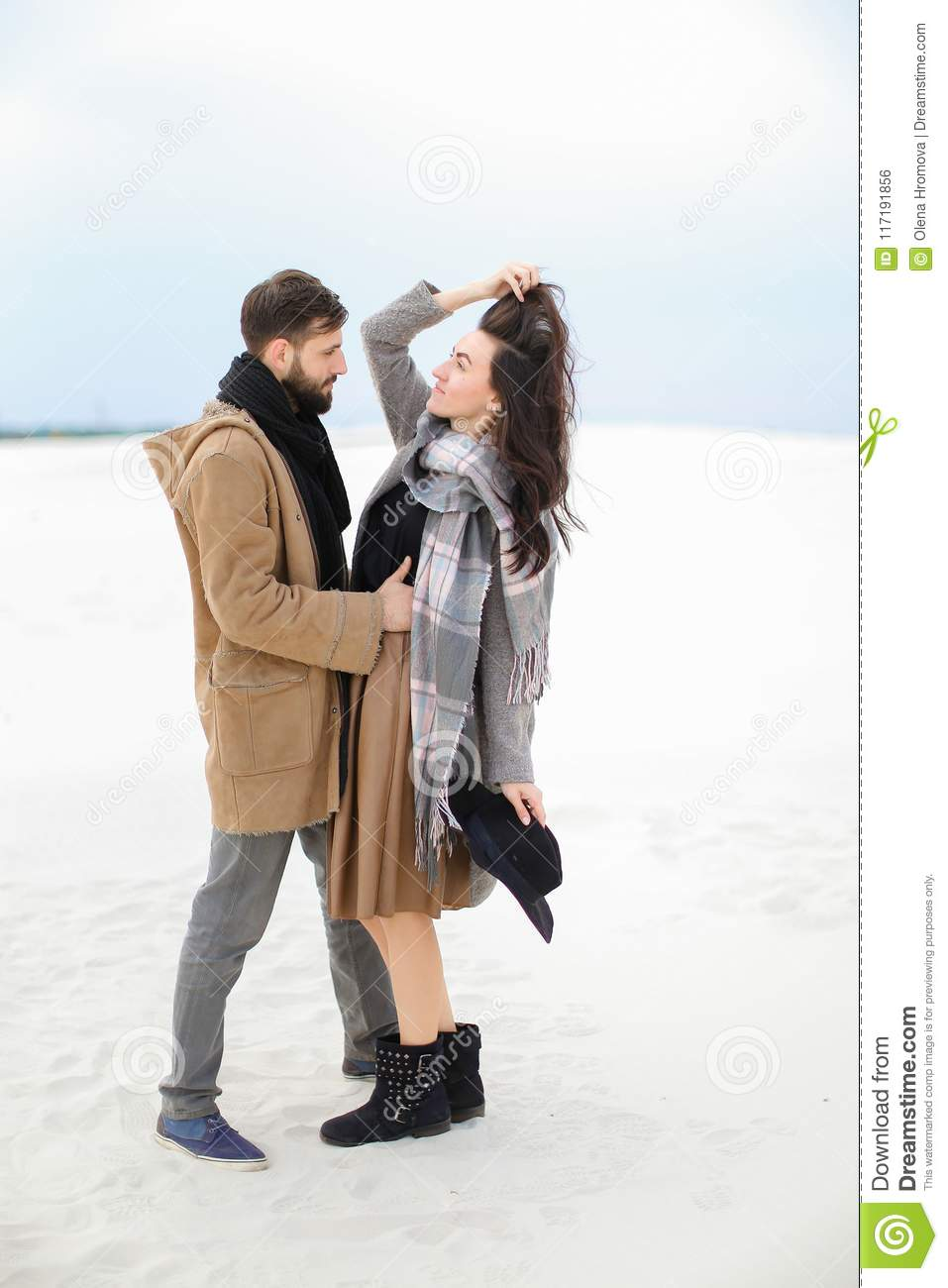 Happy woman wearing grey scarf standing with man in coat, winter white background.