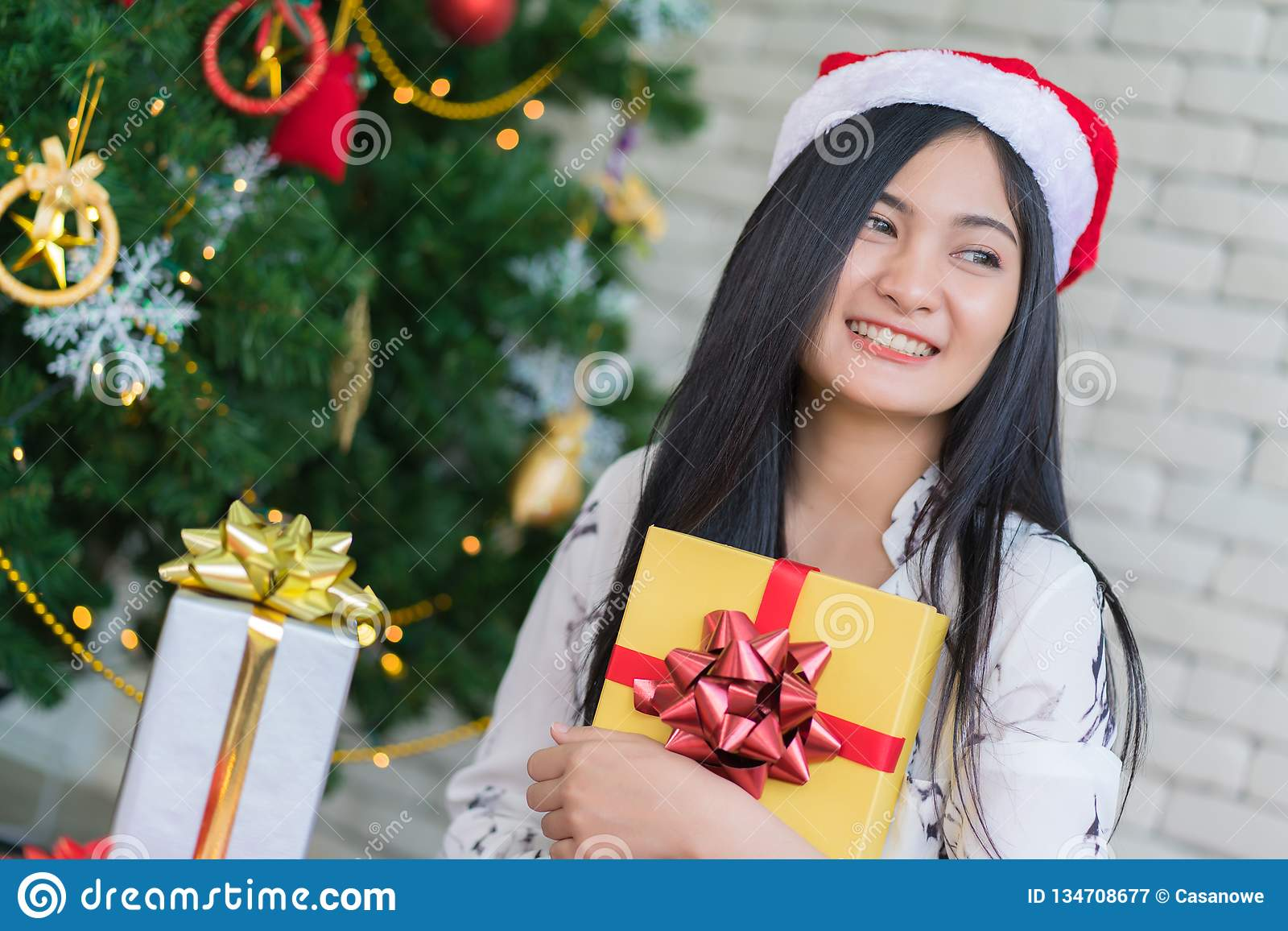 7819612bcfbe5 Happy woman wearing santa hat holding a gifts in Christmas and New Year  holiday.