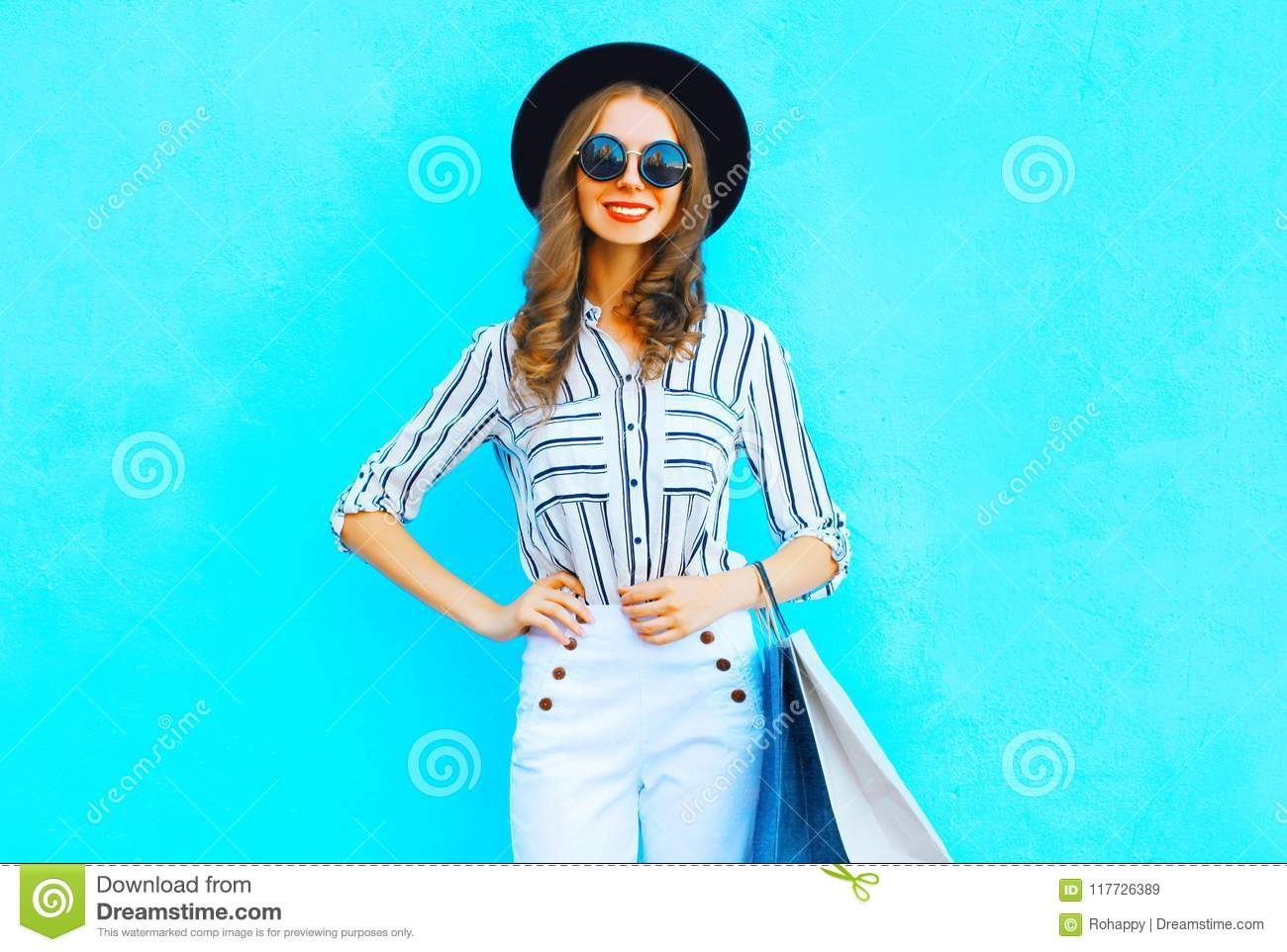 Happy woman is wearing a shopping bags, black hat, white pants