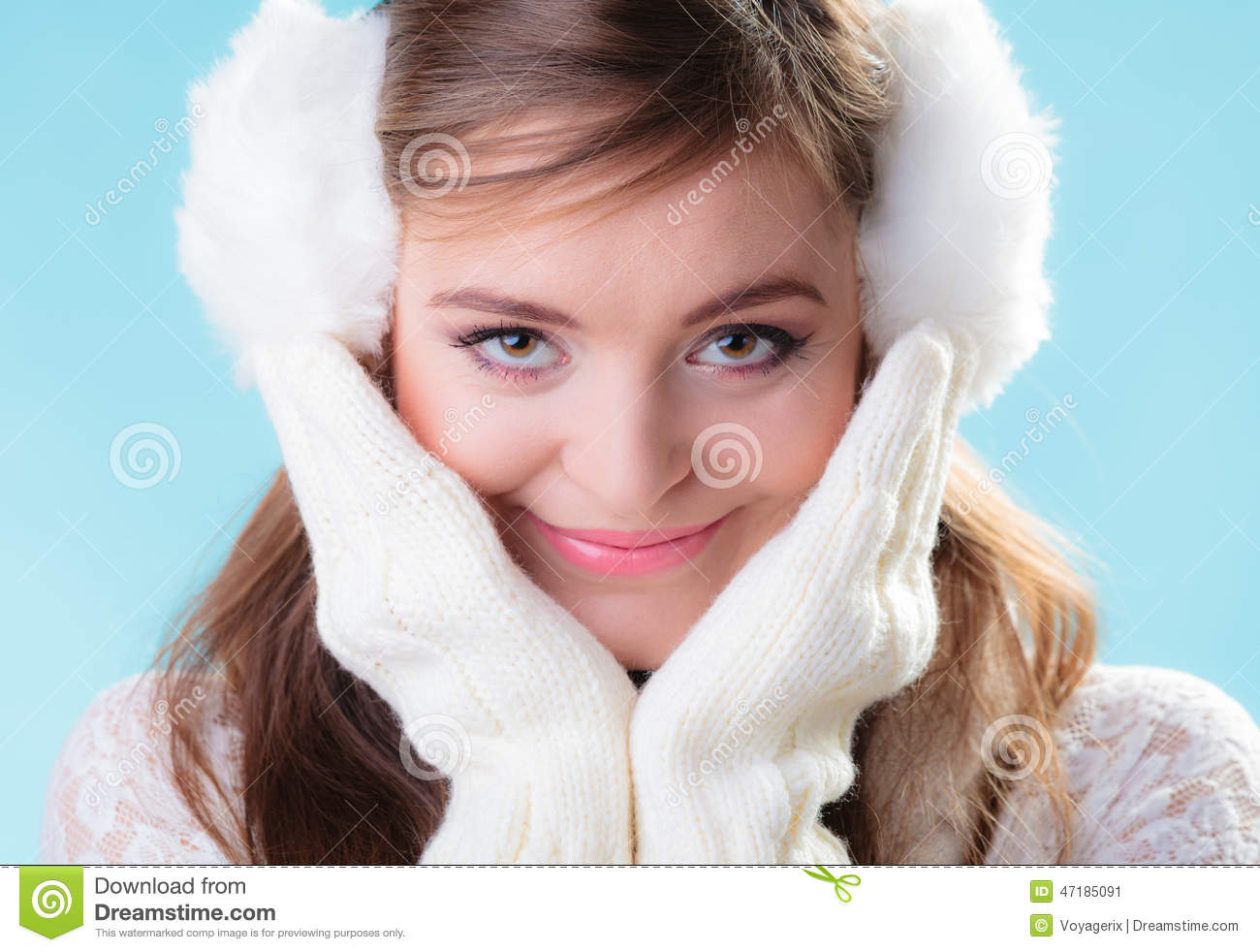 3131123bfa Portrait positive teen girl in warm clothes. Happy woman in white earmuffs  and mittens on blue