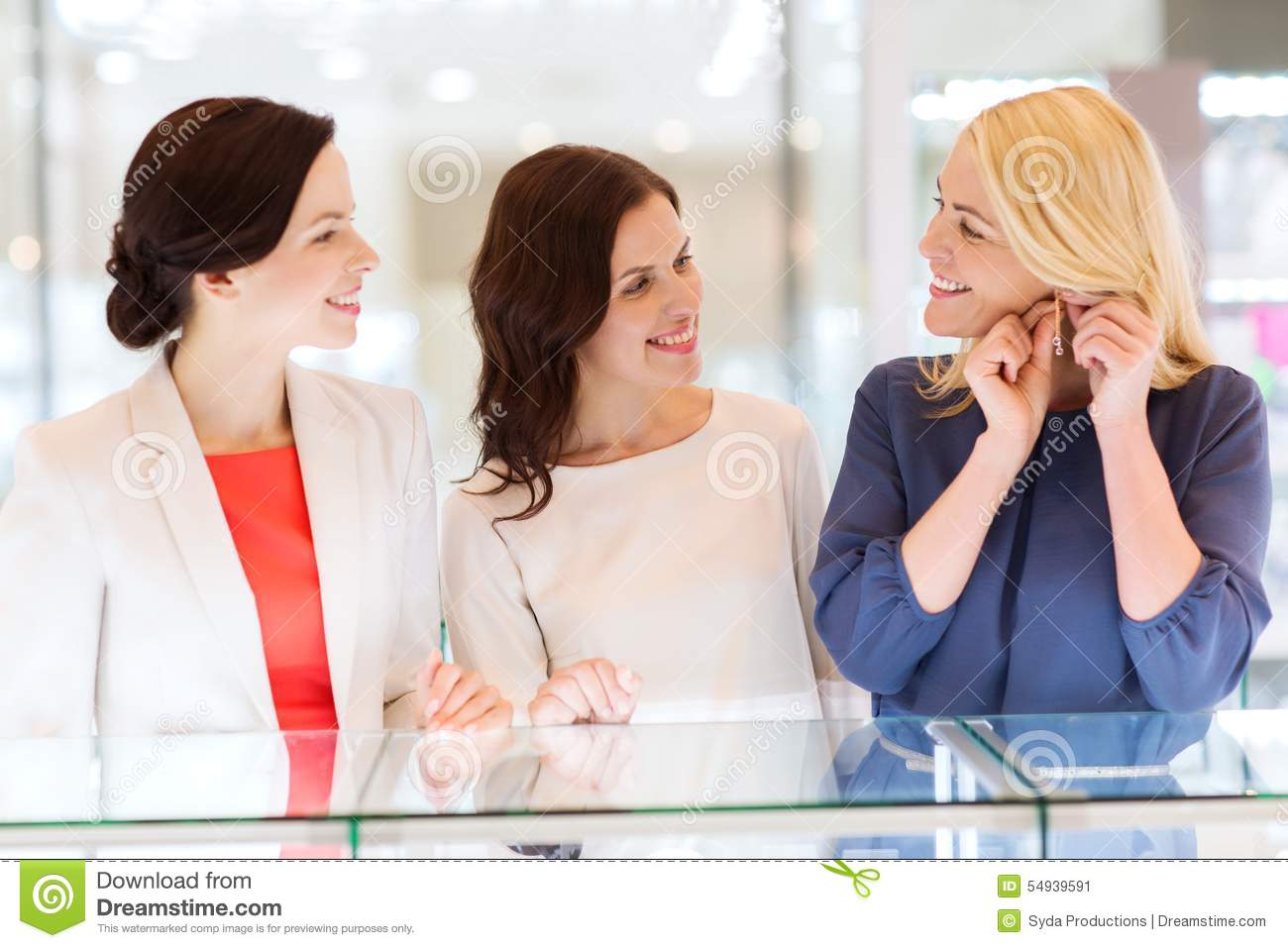 Happy women choosing earrings at jewelry store stock photo for Jewelry sale online shopping