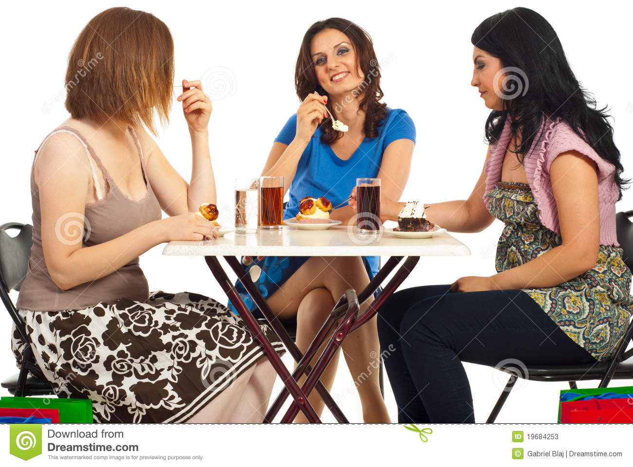 Happy women eating cakes at table