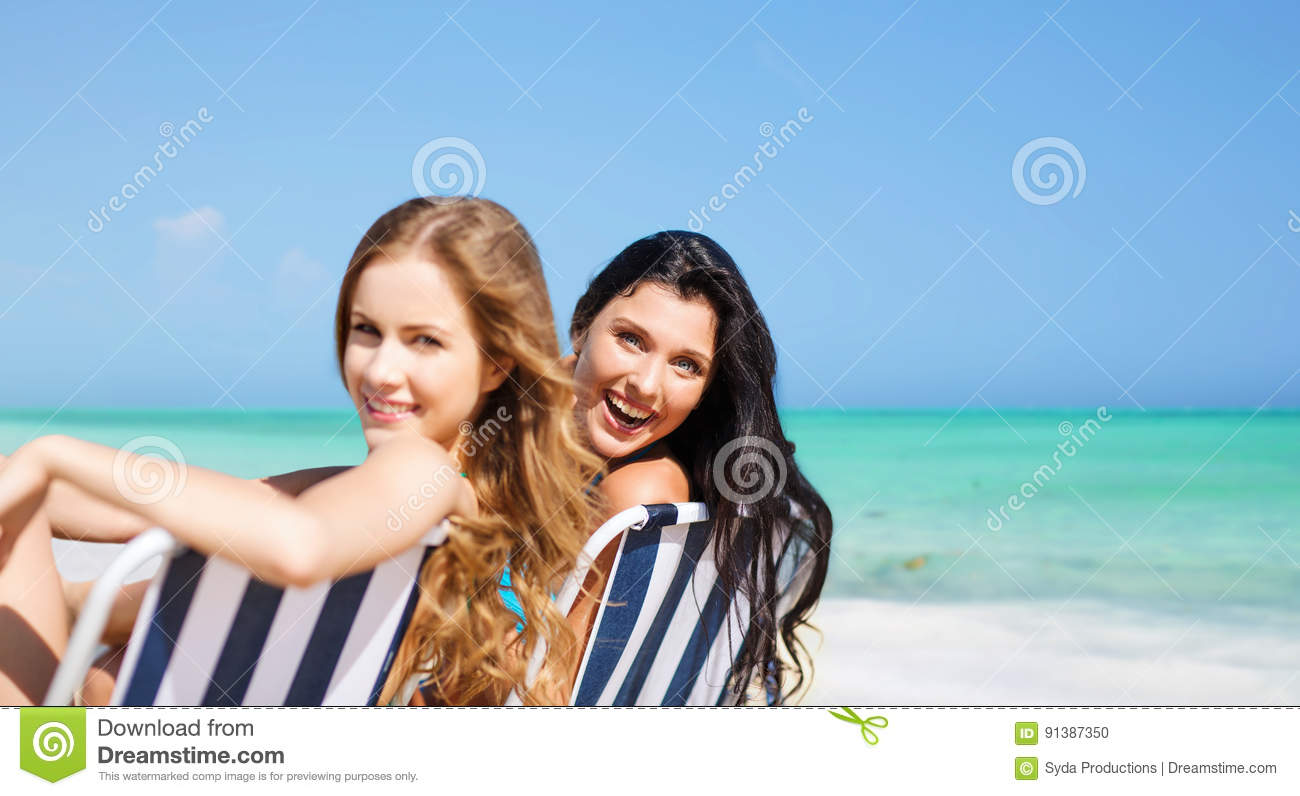 Tremendous Happy Women Sunbathing On Chairs Over Summer Beach Stock Gmtry Best Dining Table And Chair Ideas Images Gmtryco