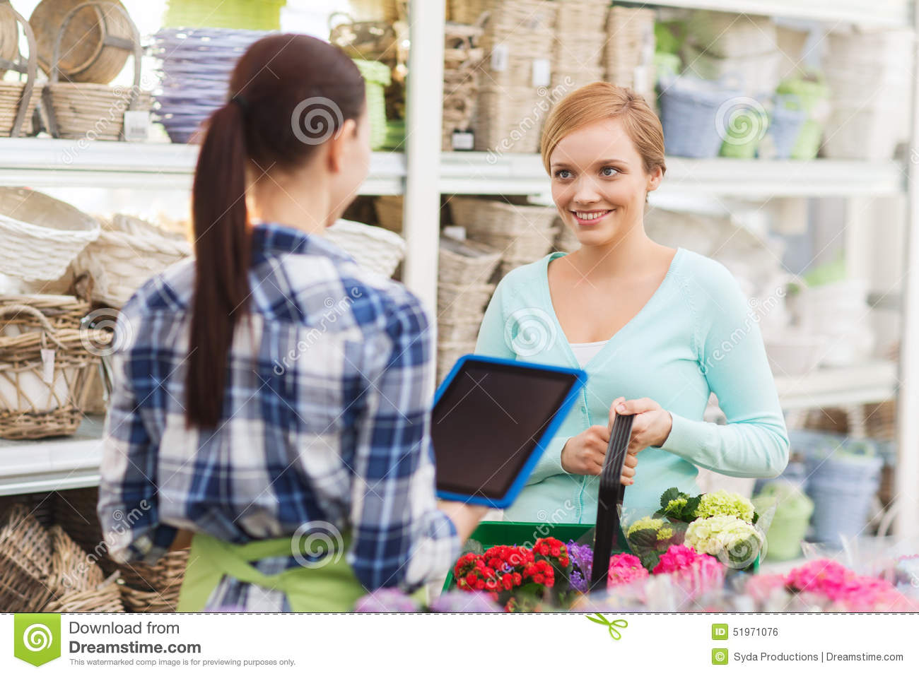 Happy women with tablet pc at flower shop