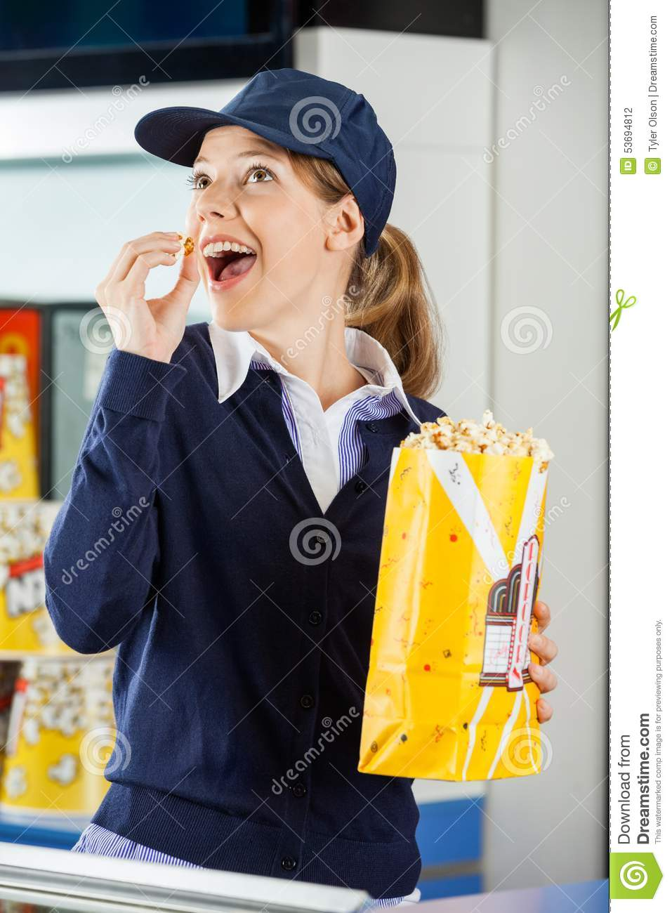 happy worker eating popcorn at cinema concession stock photo happy worker eating popcorn at cinema concession