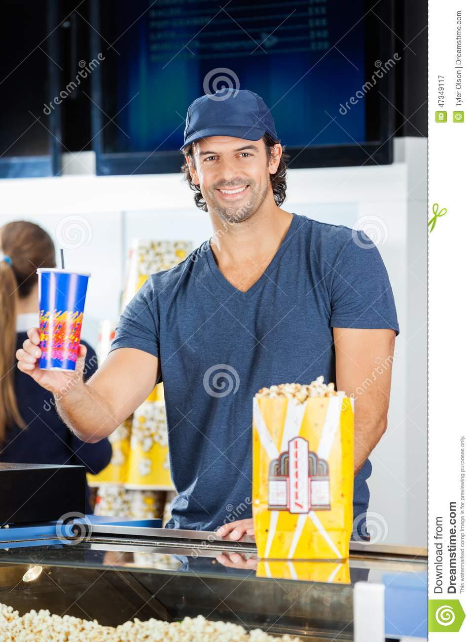 happy worker holding drink at cinema concession stock photo happy worker holding drink at cinema concession