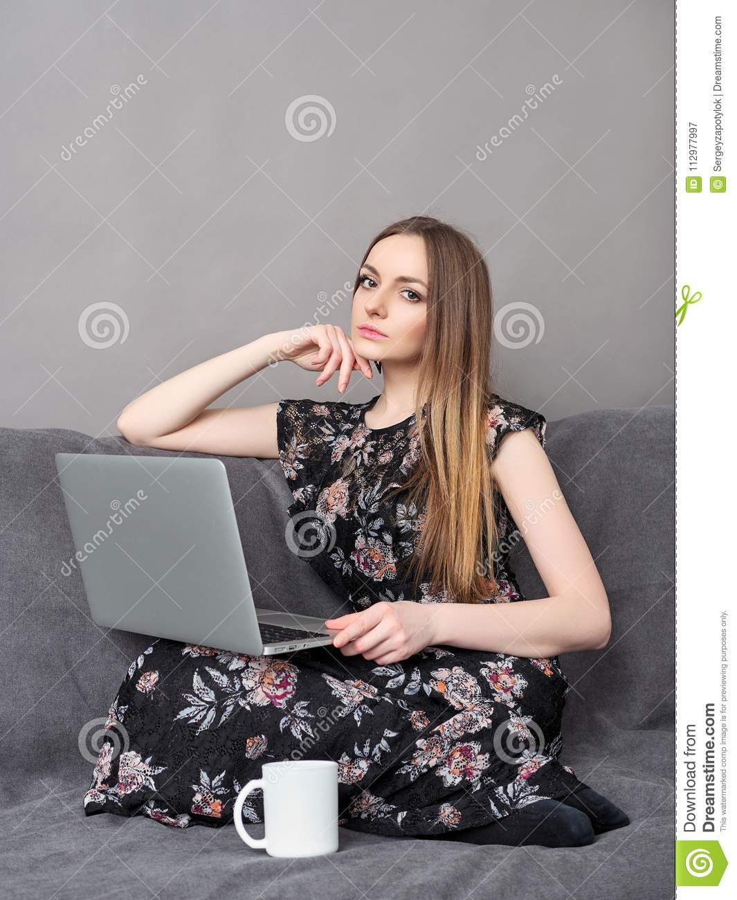 Happy young adorable woman in long dress sitting on sofa with laptop and big white mug at home