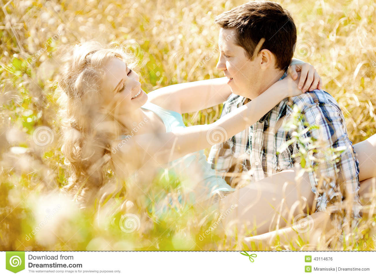 Happy young adult couple in love on the field. Two, man and wom