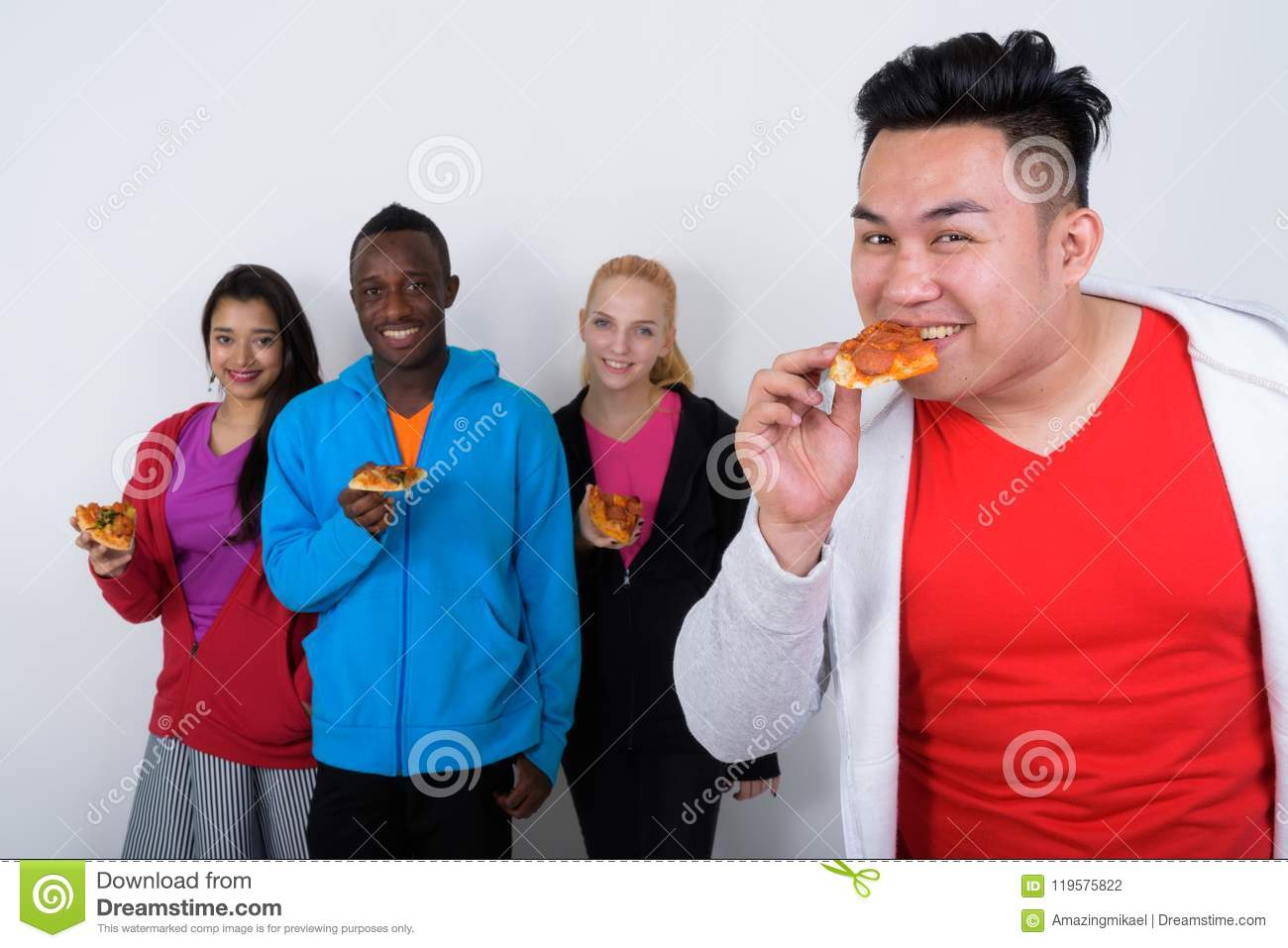 Happy young Asian man eating slice of pizza with diverse group o