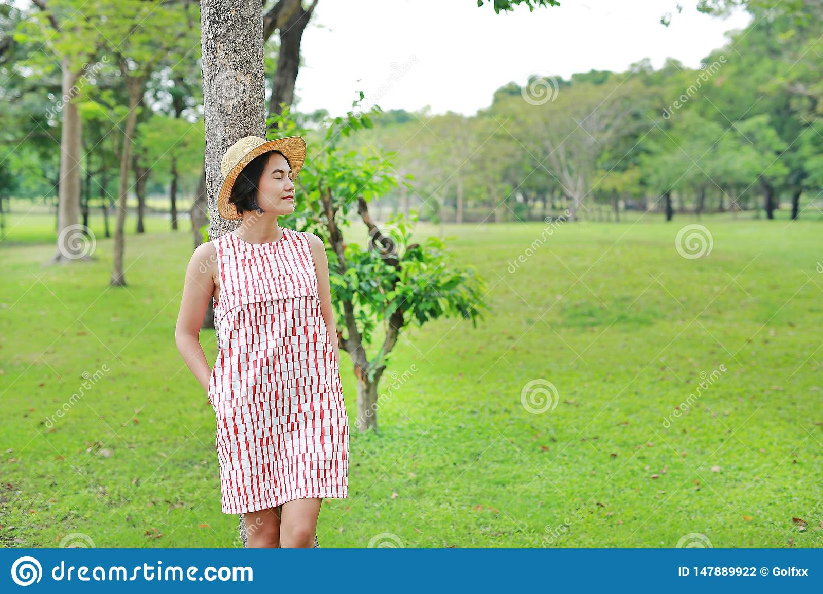 Happy young Asian woman relaxing in the summer garden. Close eyes