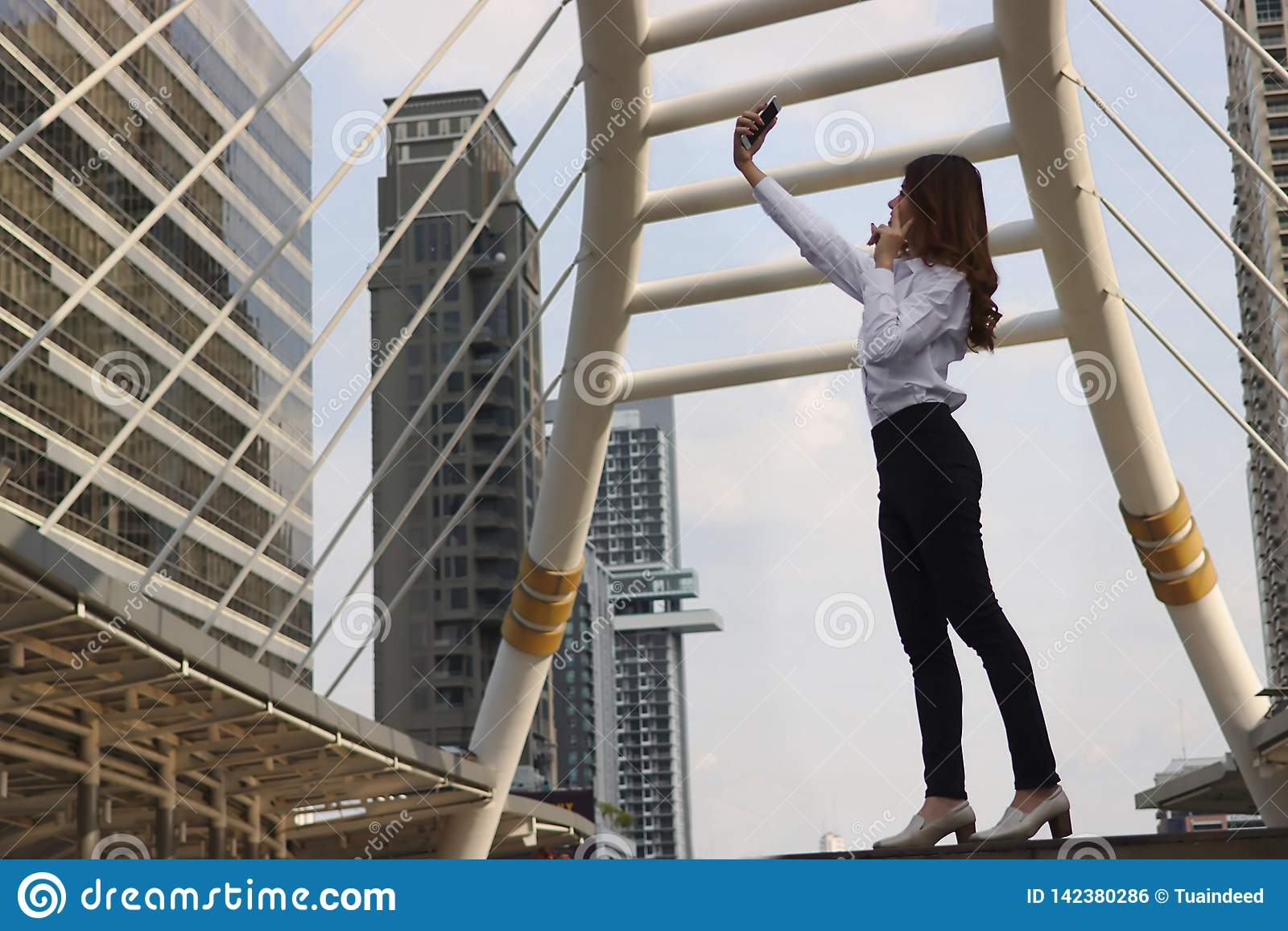 Happy young Asian woman taking a selfie photo at urban building with copy space background