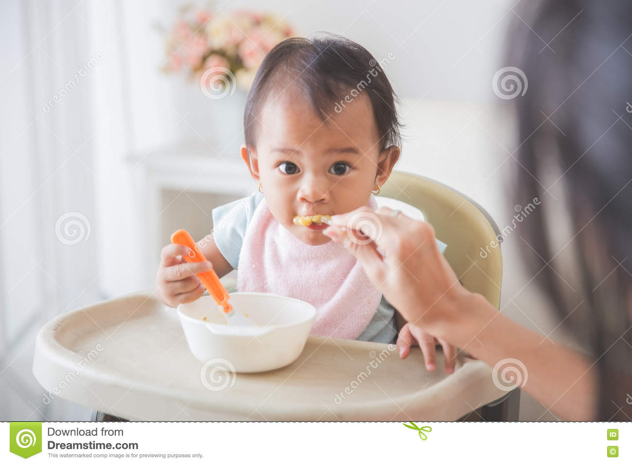 Happy Young Baby In High Chair being fed