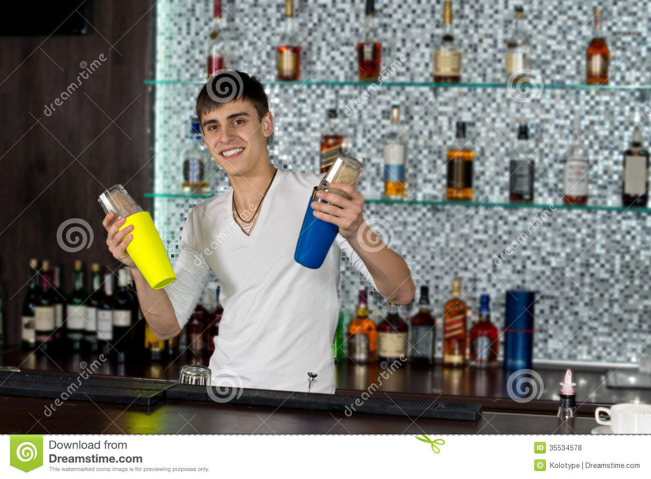Happy young barman mixing cocktails