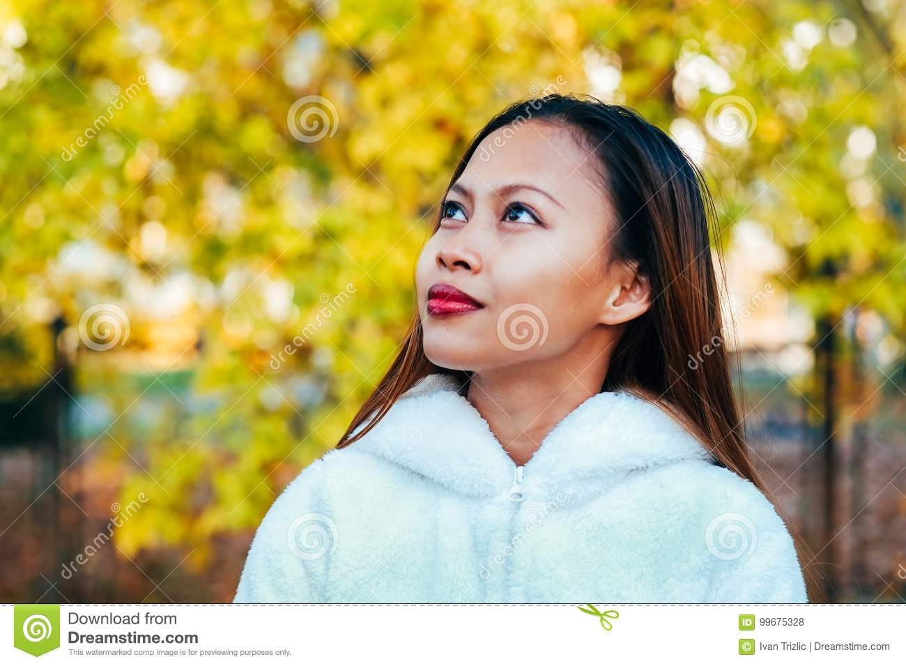 Happy young beautiful woman in autumn park on sunny day, Young woman in white coat during sunset in the park