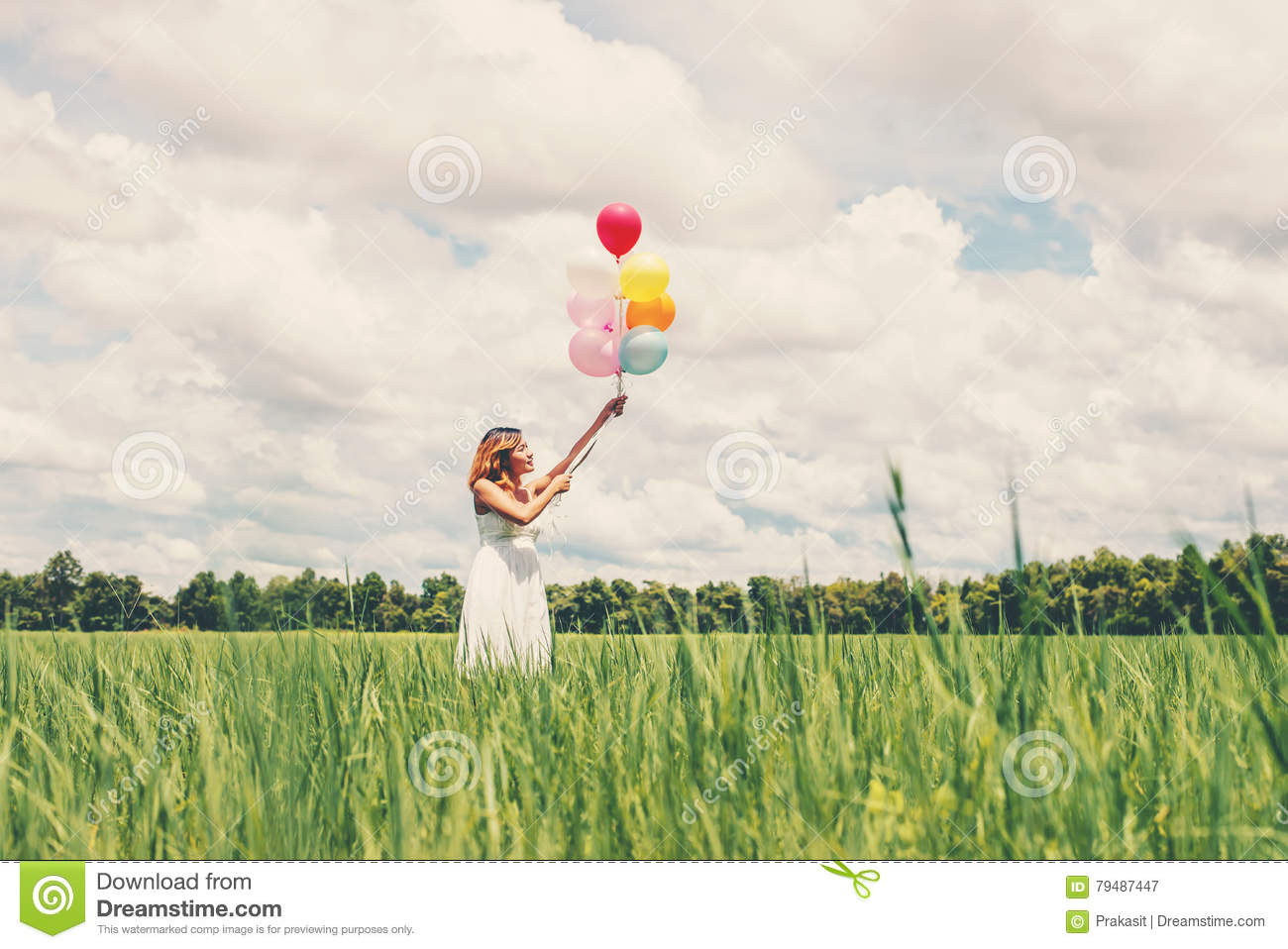 Happy young beautiful woman holding balloons in the grass field