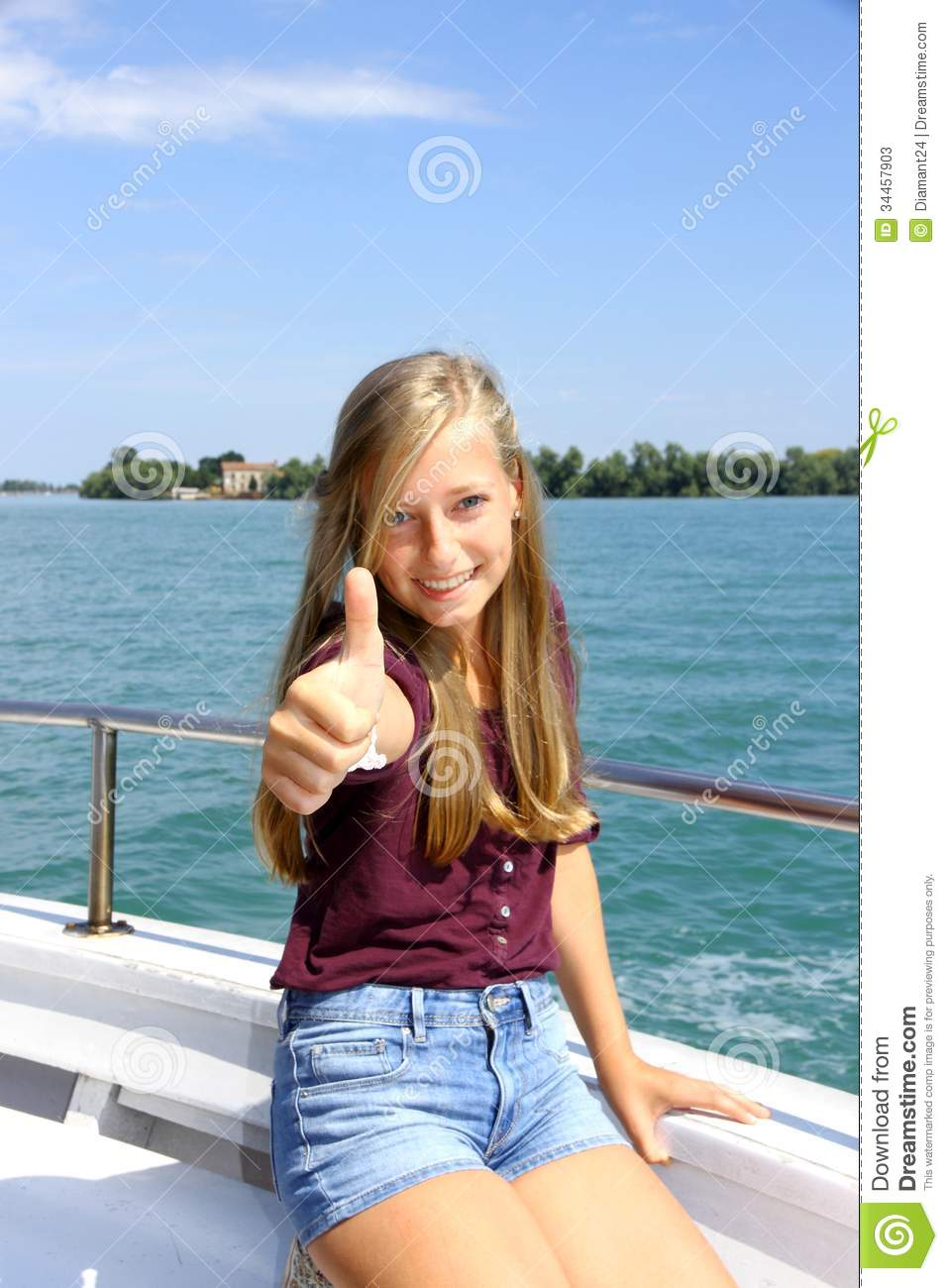 Young Blonde Teen Aged Girl Smiling At The Beach Stock: Happy Young Blonde Girl Shows Ok Sign On Ship At Sea Stock