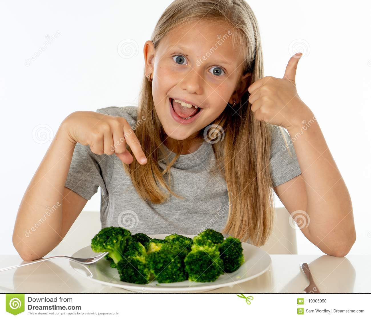 d9cdba7f Happy young blonde girl with thumbs up enjoying and loving eating her broccoli  vegetables on a plate with knife and fork in healthy children eating concept