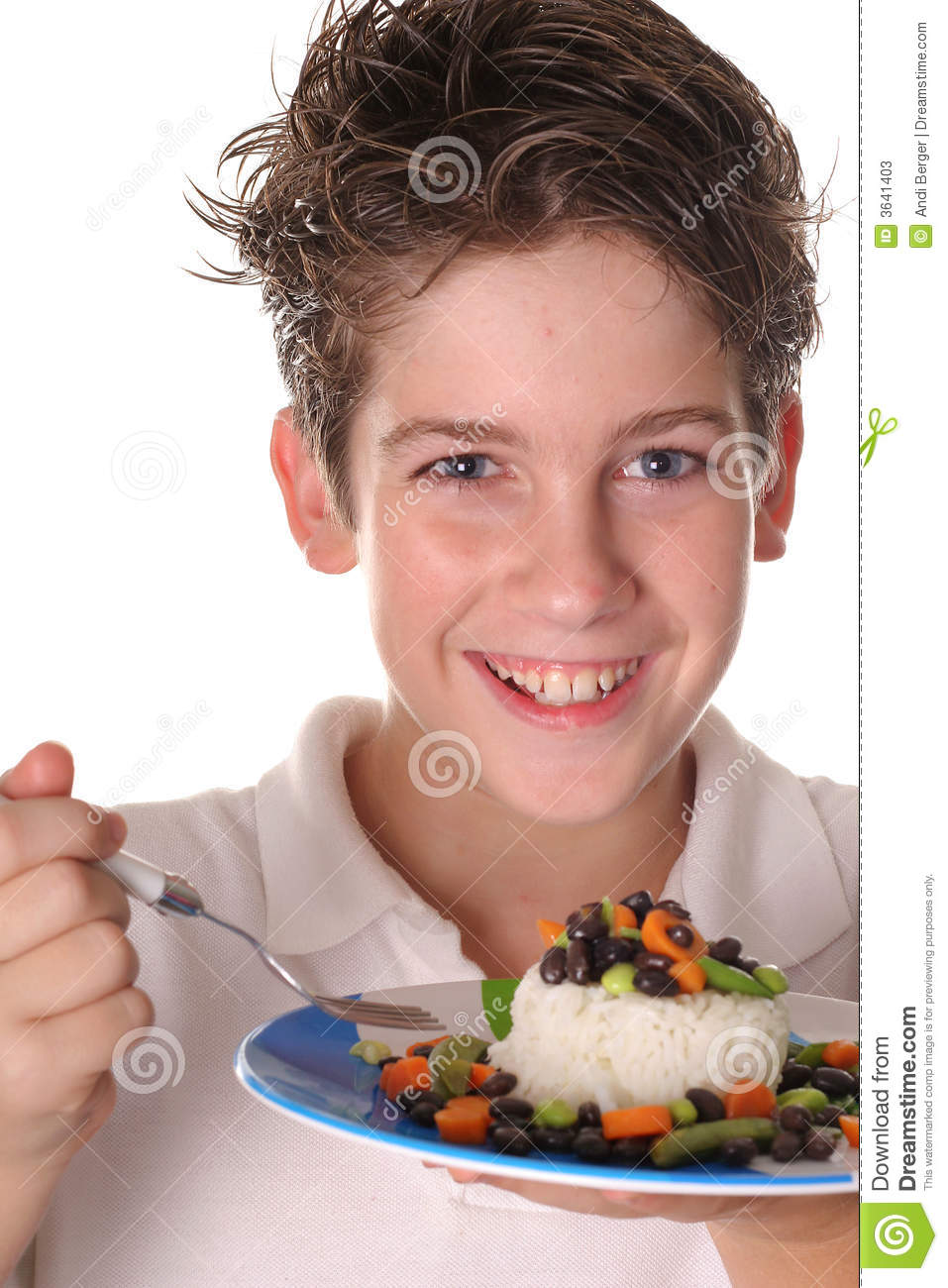 Happy young boy eating healthy rice, beans & veggi
