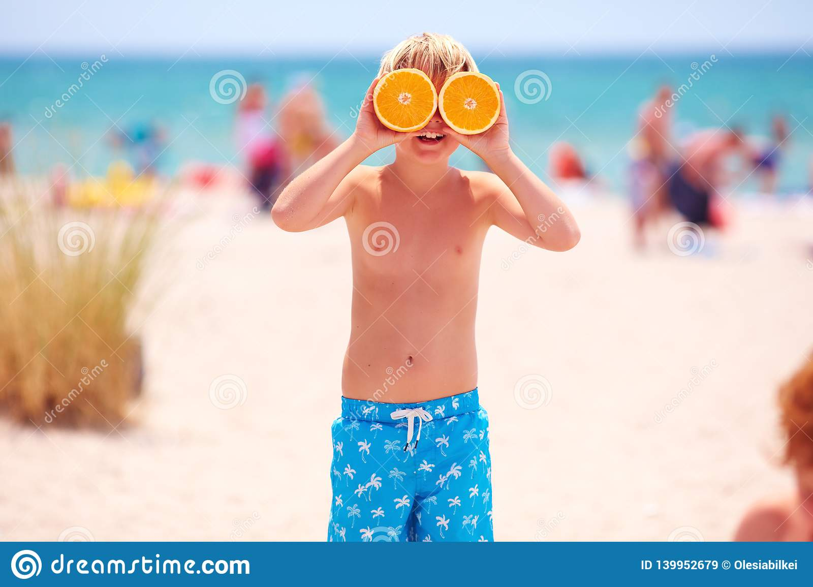 Happy young boy, kid with citrus eyes on sandy beach during summer vacation