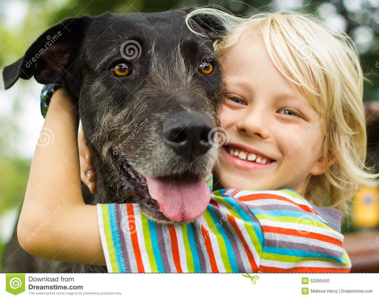 Happy young boy lovingly hugging his pet dog