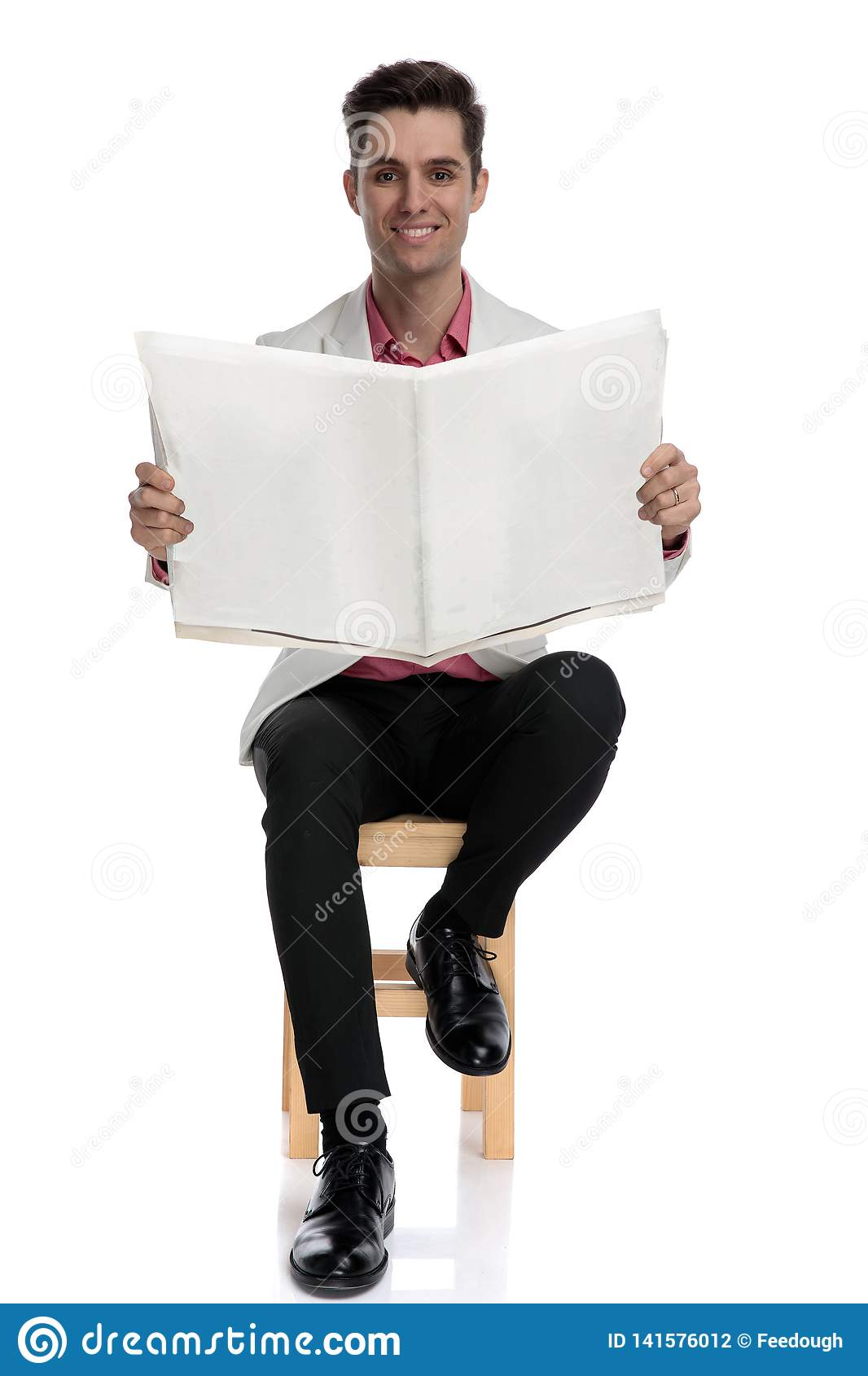 Happy young businessman reading newspaper while sitting