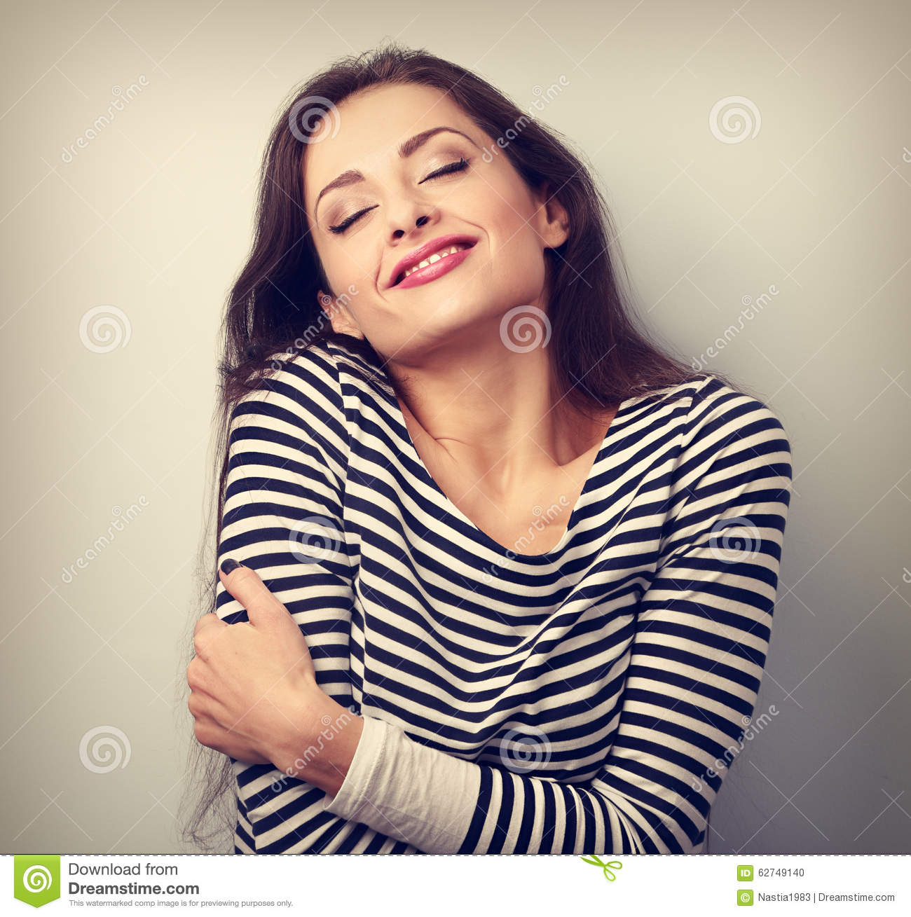 Happy young casual woman hugging herself with natural emotional