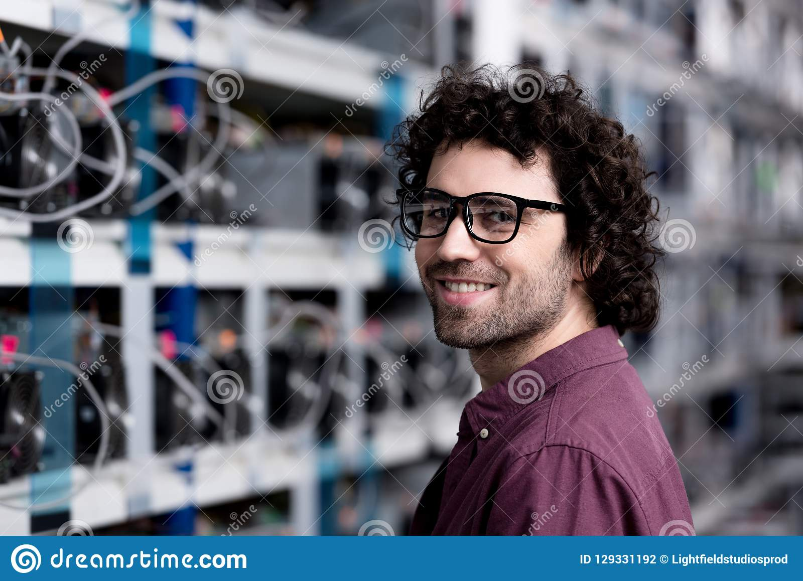 Happy young computer engineer at cryptocurrency mining farm looking at camera stock photography
