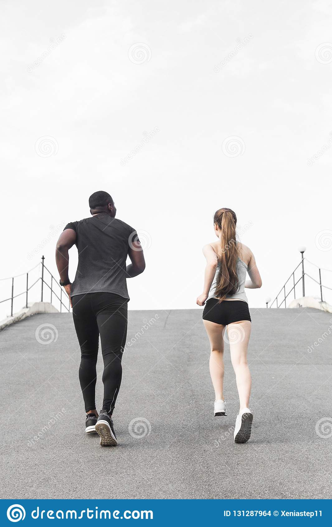 Happy young couple afro-american man and european woman running together. A loving couple is run, engaged in sports