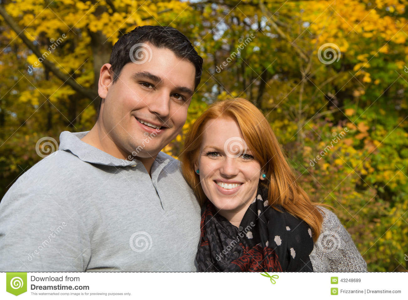 Happy young couple in autumn making a walk on the fresh air.