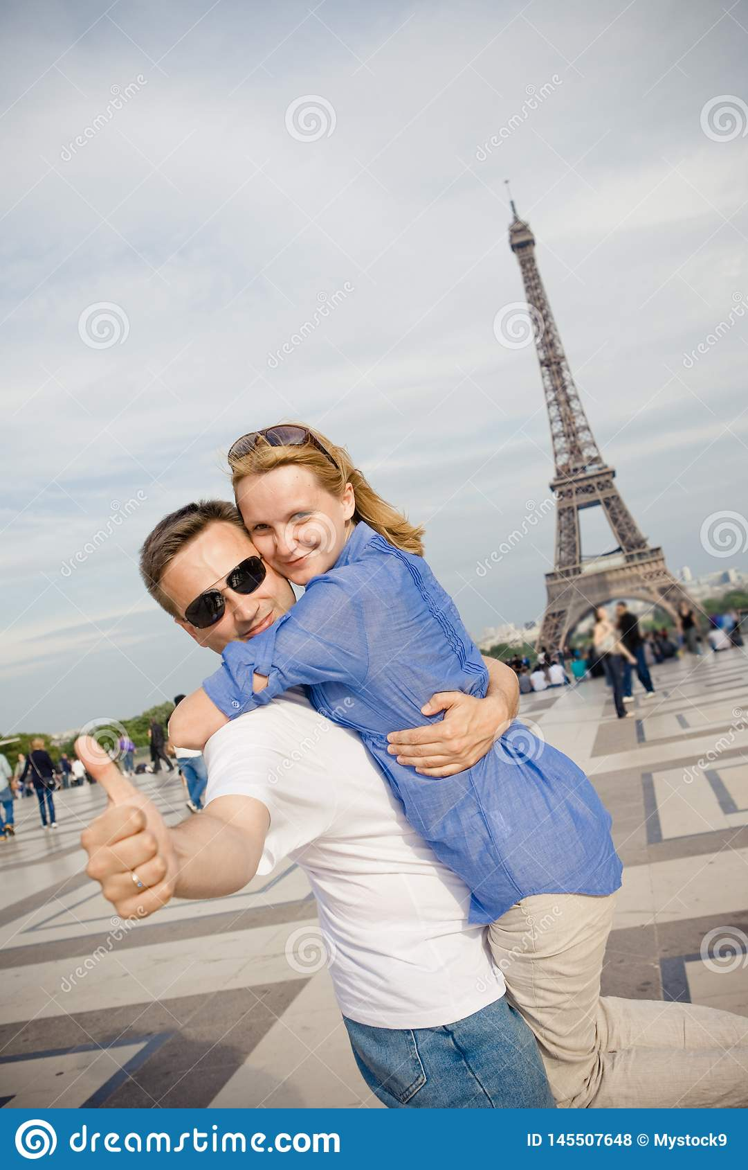 Happy young couple on the background of the Eiffel Tower in Paris. Honeymoon in Europe
