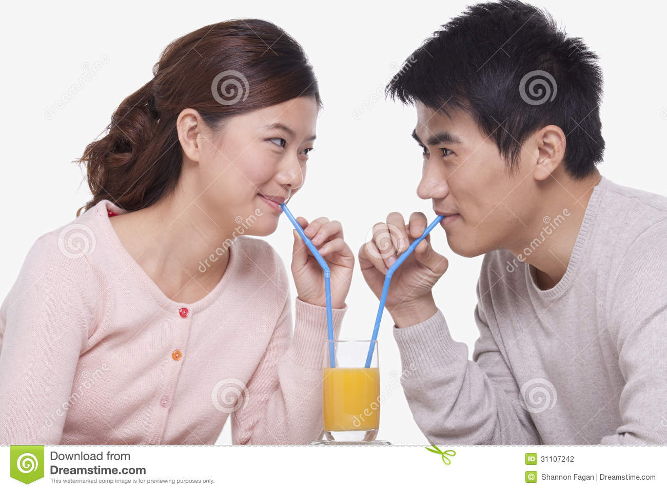 Happy Young Couple Bonding And Sharing A Glass Of Orange