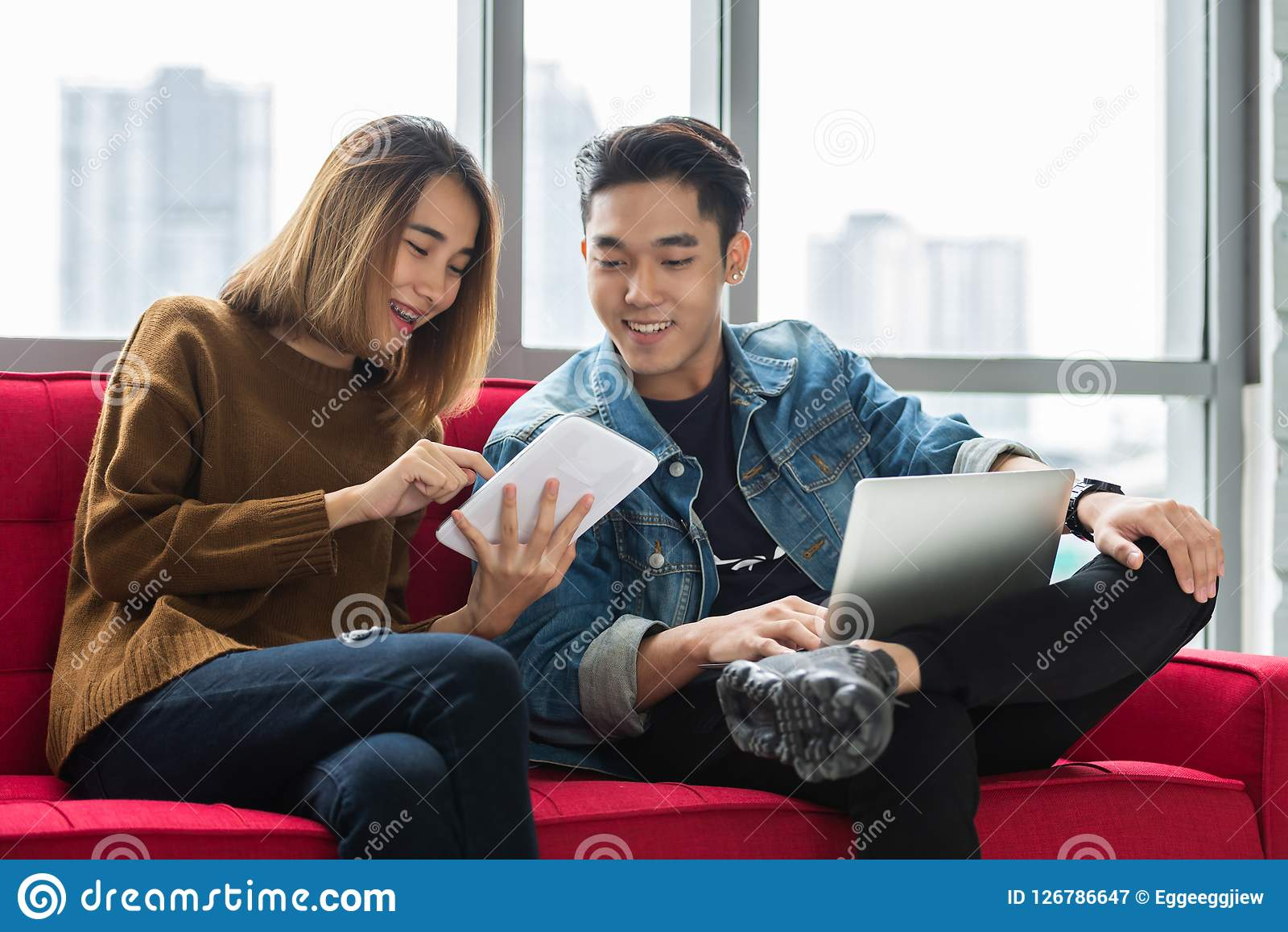Happy Young couple designer using digital tablet and laptop together.