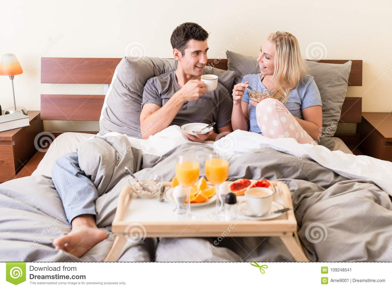 Happy young couple drinking coffee and orange juice