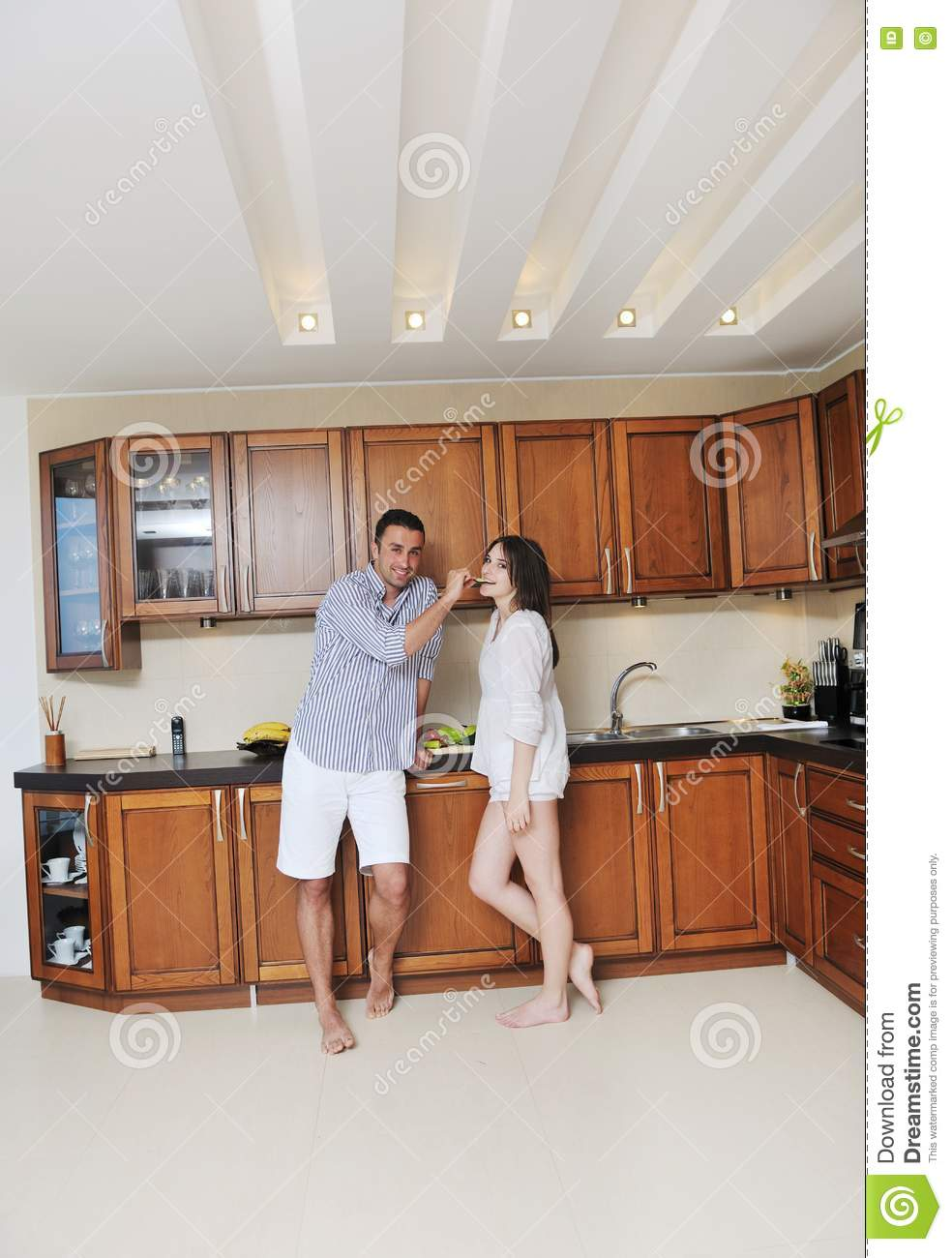 Happy young couple have fun in modern kitchen
