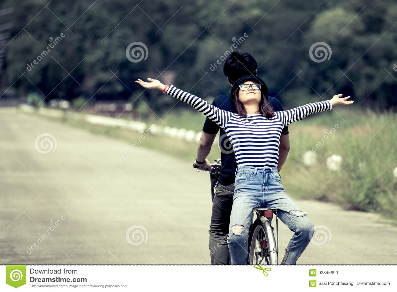 Happy young couple of hipsters riding a bicycle together