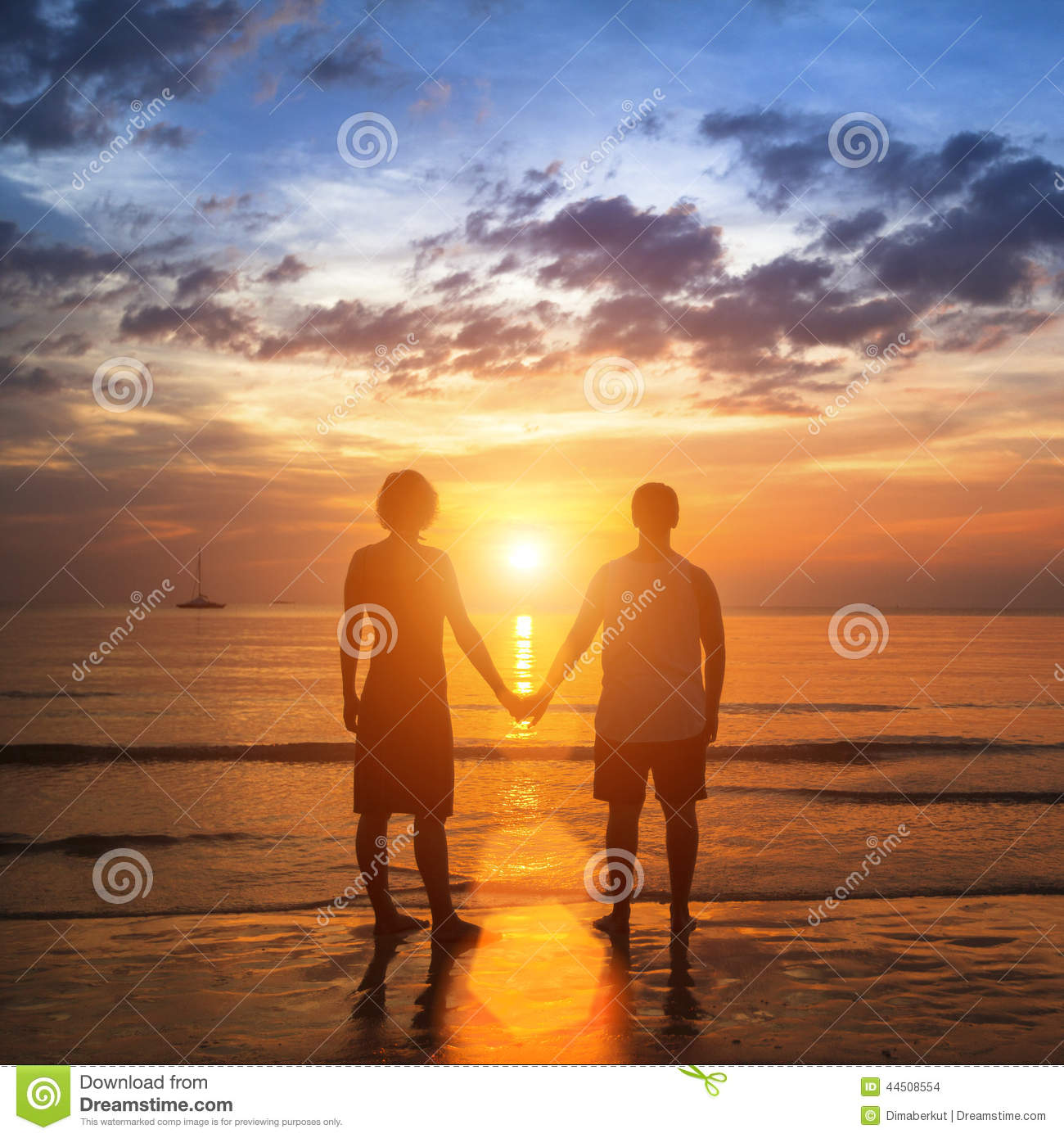 Happy Young Couple Holding Hands On Sea Beach During The