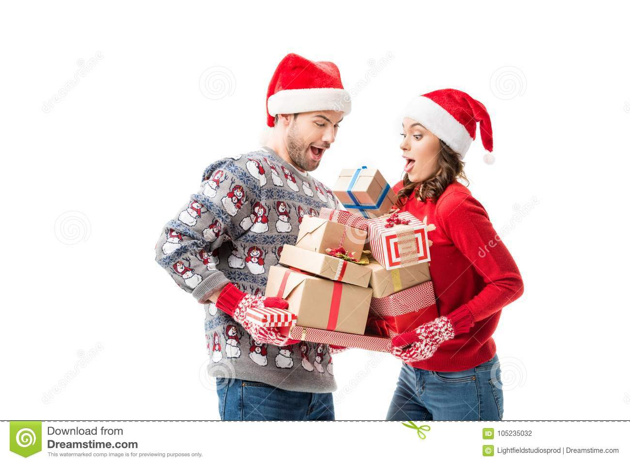 happy young couple holding stacks of christmas gifts isolated on white
