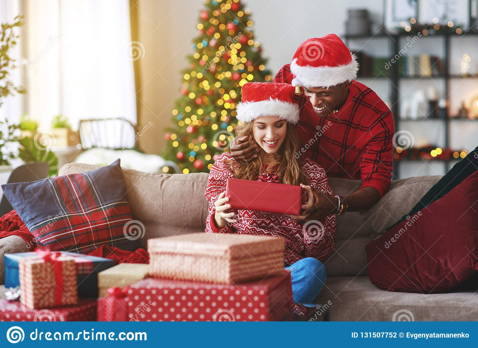 Happy young couple opening presents on Christmas morning