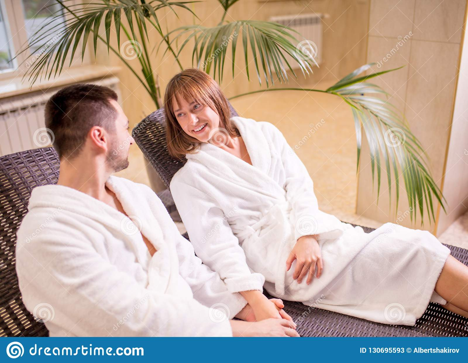 Happy young couple relaxing together at day spa
