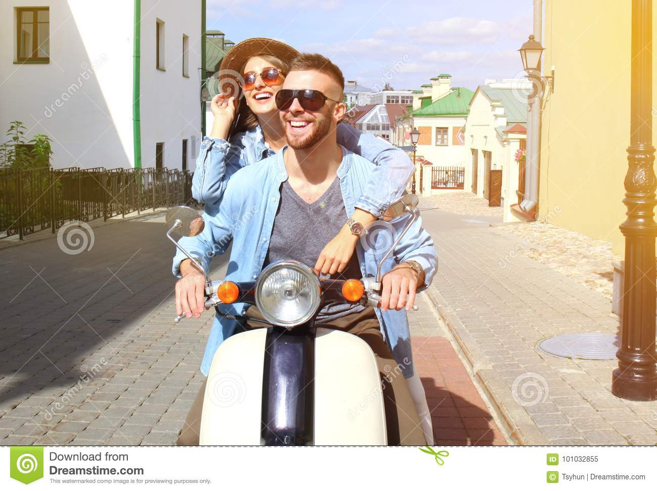 Happy young couple riding scooter in town. Handsome guy and young woman travel. Adventure and vacations concept.