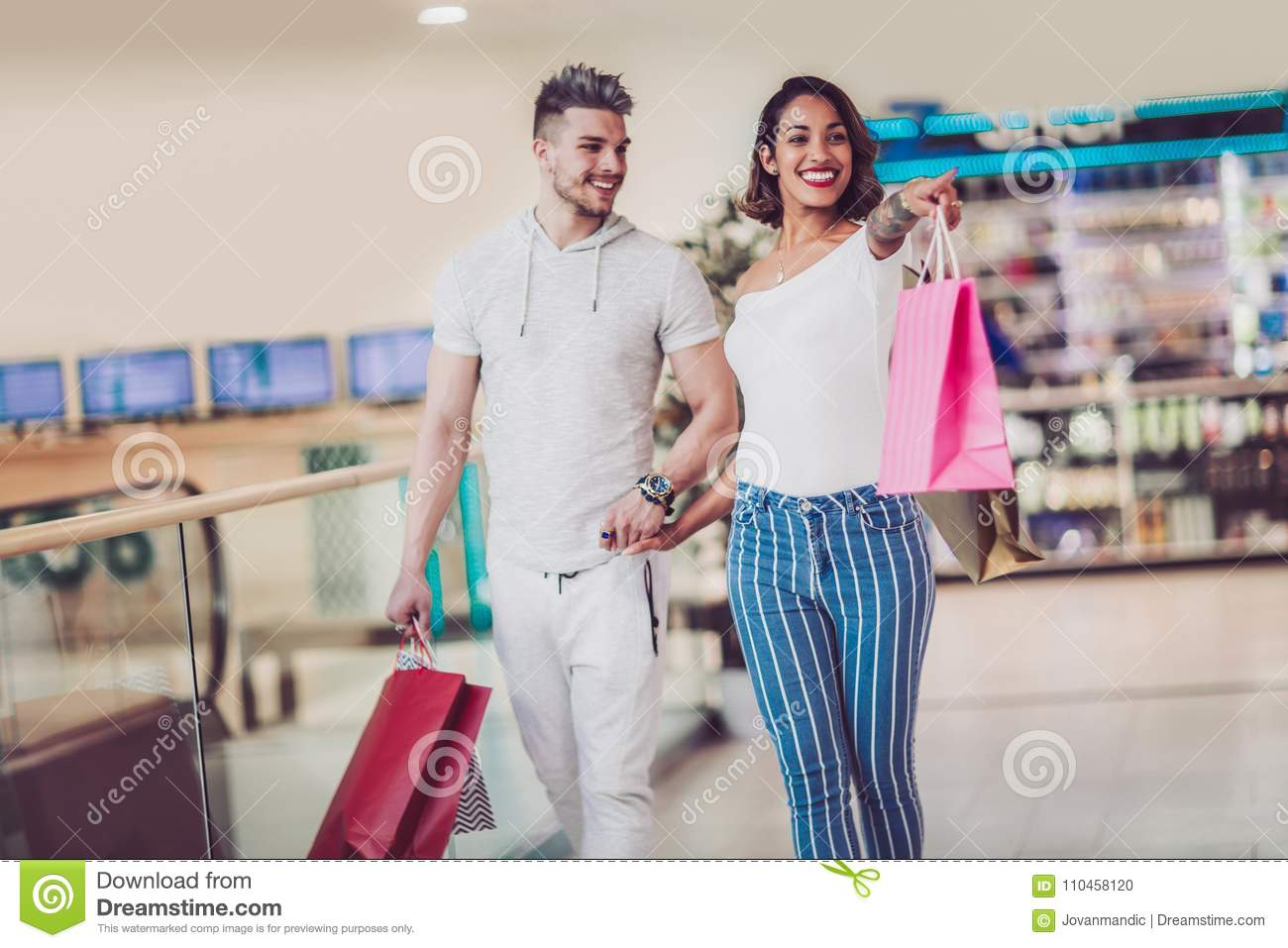 c2e13e7e6c Happy Young Couple With Shopping Bags Walking In Mall Stock Photo ...
