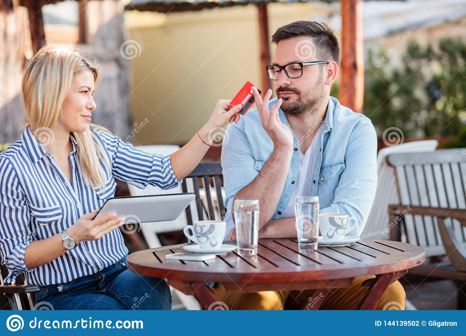 Happy young couple sitting in a cafe and shopping online