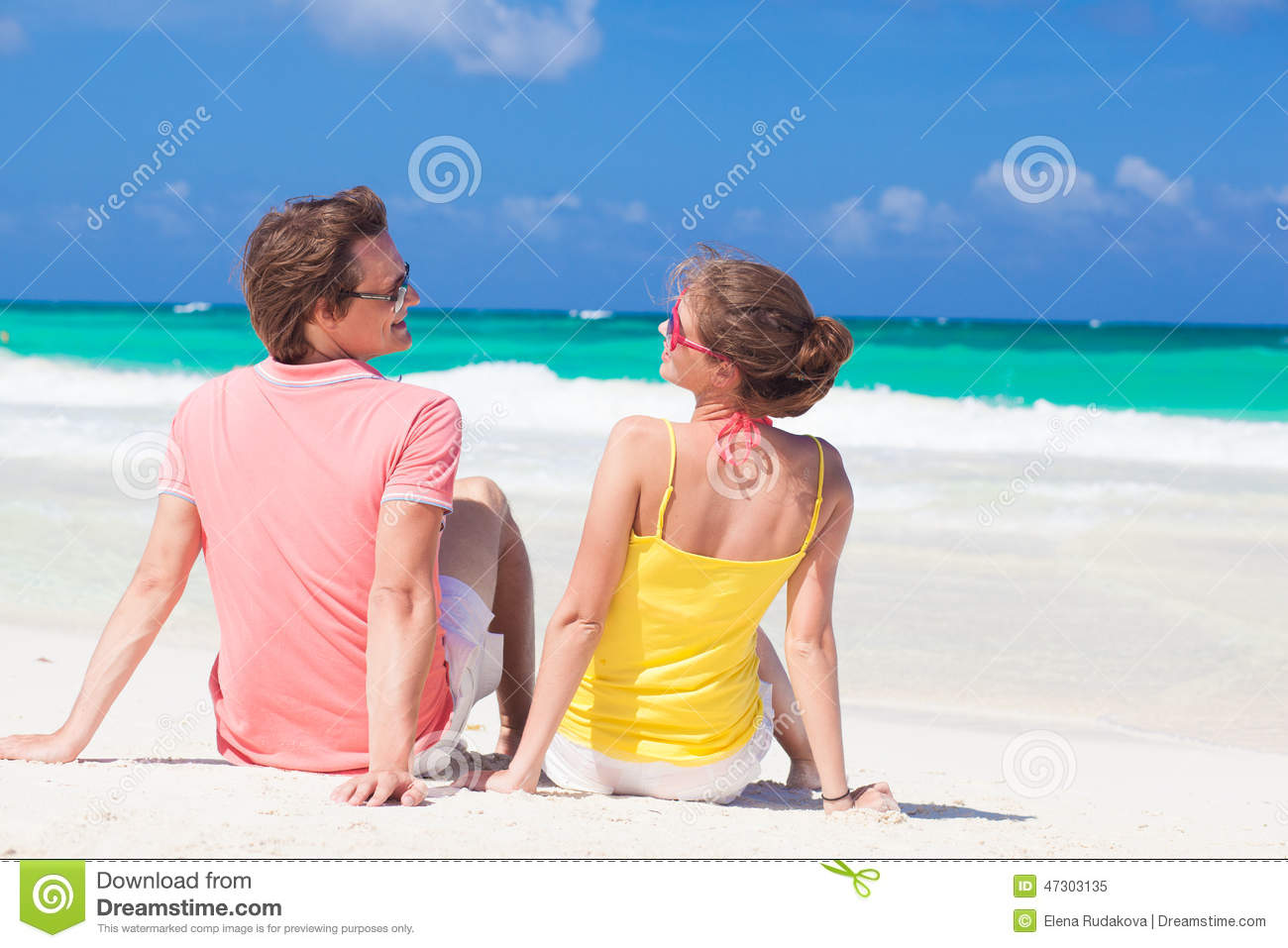 Happy young couple sitting at tropical beach stock photo for Tropical vacations for couples
