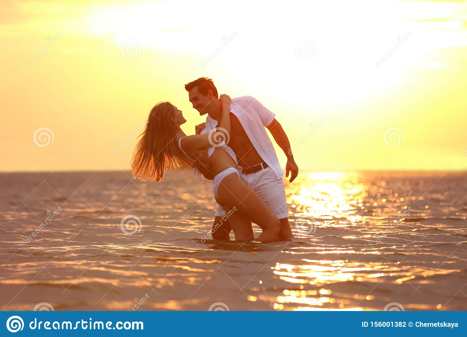 Happy young couple spending time on sea beach at sunset